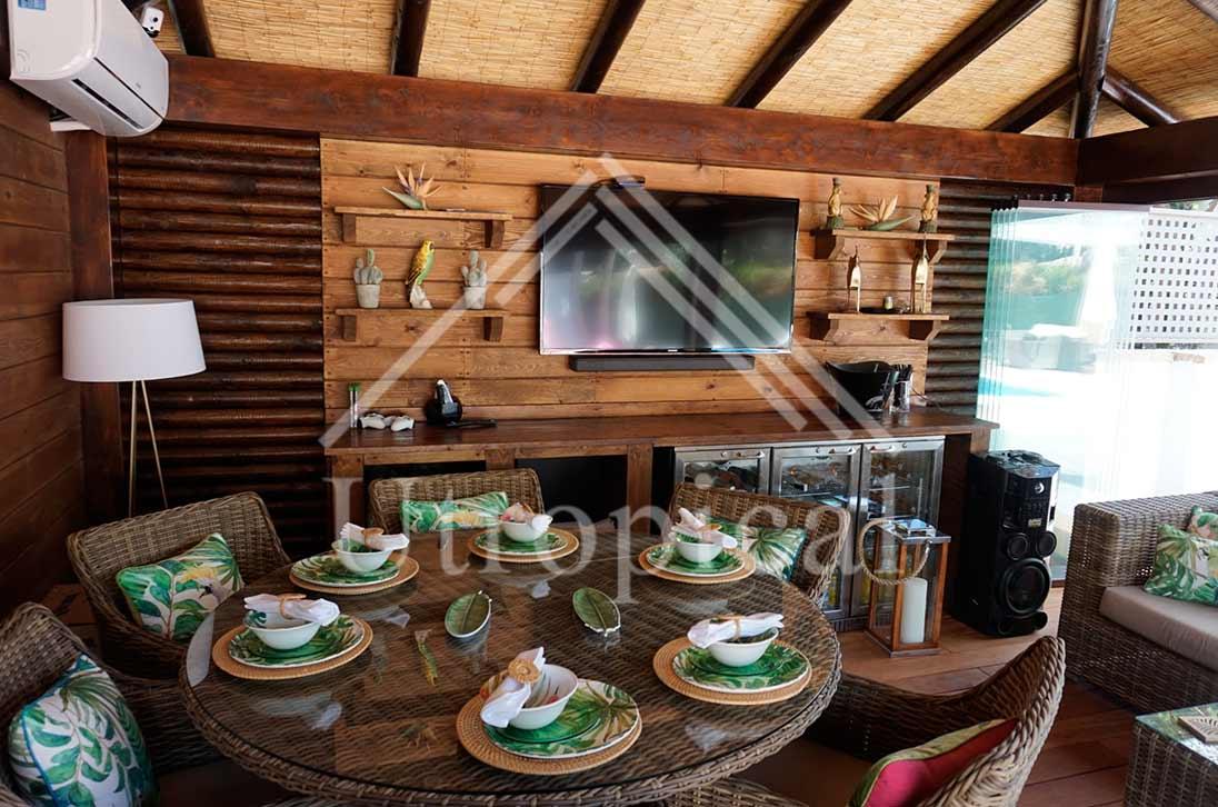 cenador de madera con cristales y tejado de junco